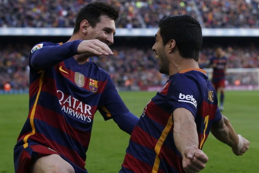Pemain Barcelona Luis Suarez dan rekan setimnya Lionel Messi merayakan kemenangannya atas Atletico Madrid, Sabtu (30/1), di Camp Nou.