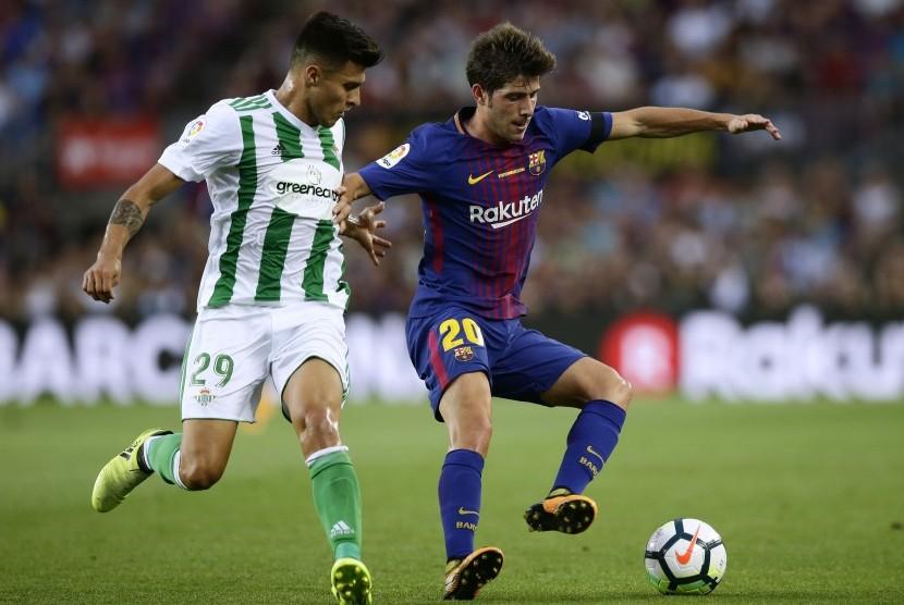 Pemain Barcelona Sergi Roberto (kanan) berduel dengan pemain Real Betis Juanjo Narvaez di La Liga Spanyol di Camp Nou, (20/8).