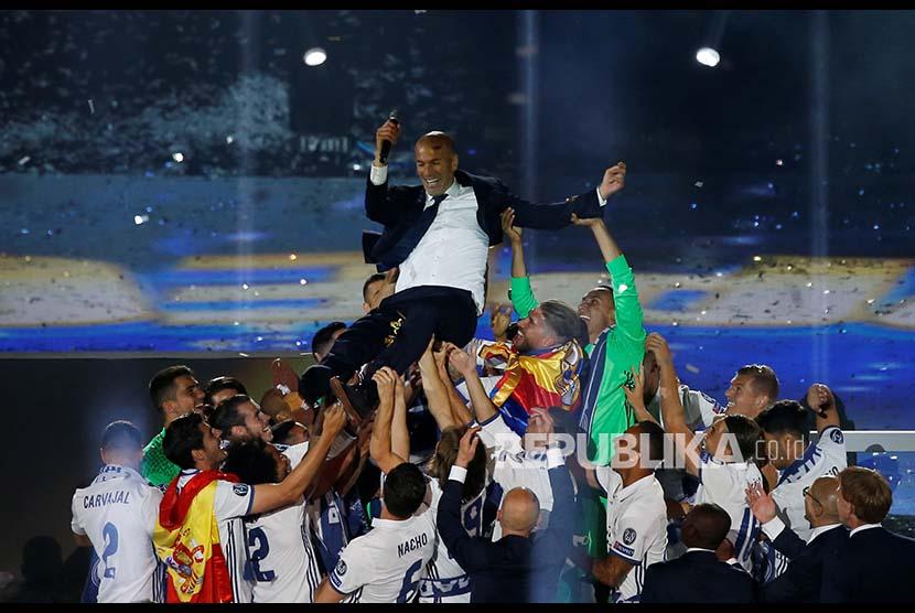 Pemain dan tim Real Madrid melemparkan pelatih mereka ke udara saat merayakan kemenangan ke-12 Real Madrid di ajang Liga Champions Eropa.