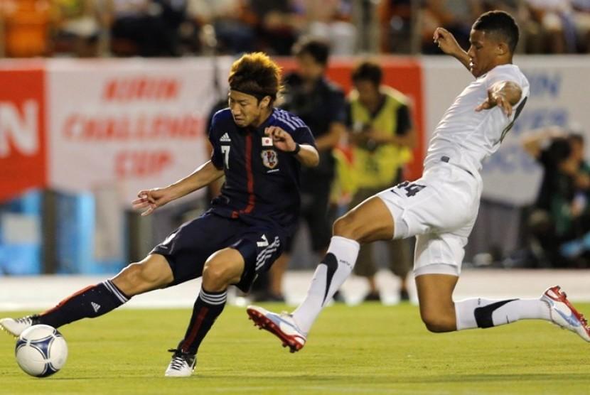 Pemain Jepang, Yuki Otsu (kiri) berebut bola dengan pemain Selandia Baru, James Musa dalam pertandingan persahabatan di Tokyo, 11 Juli 2012