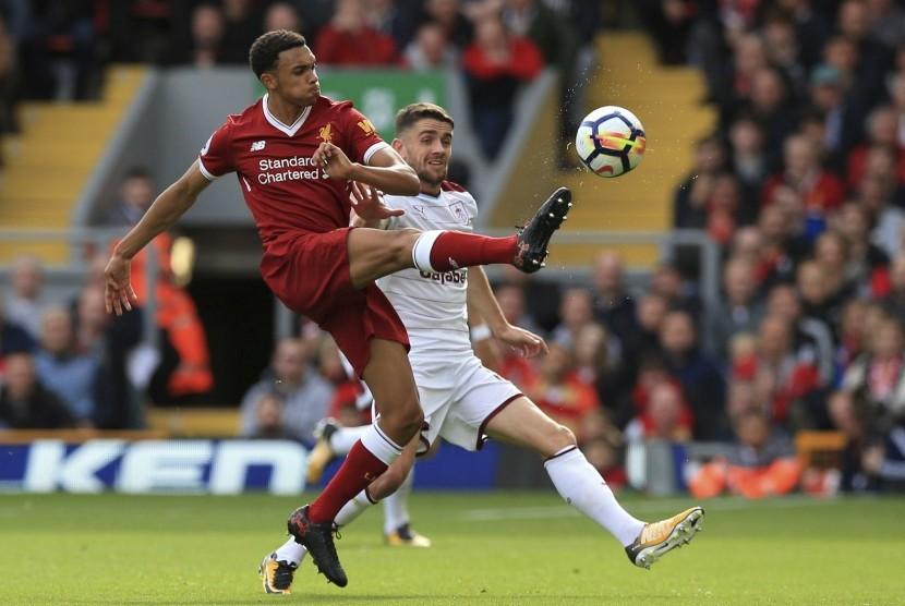 Pemain Liverpool Trent Alexander-Arnold (kiri) berebut bola dengan pemain Burnley dalam lanjutan Liga Primer Inggris, Sabtu (16/9).