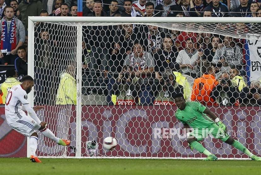 Pemain Lyon Alexandre Lacazette mencetak gol dari titik penalti  ke gawang yang dijaga Andre Onana (kanan)  dalam pertandingan semifinal Europa League di Stadion Old Trafford, Jumat (12/5) dini hari.