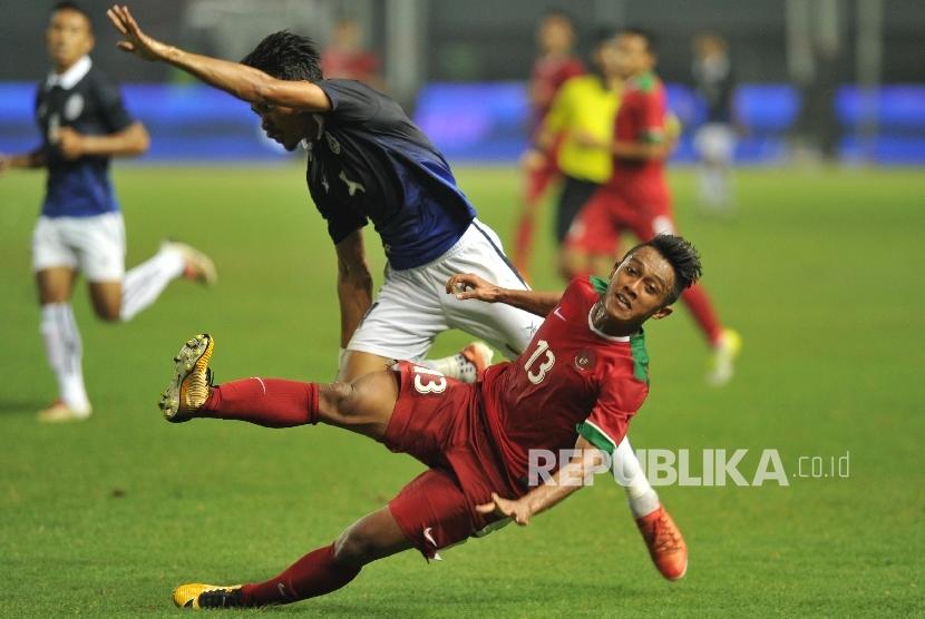 Pemain timnas Indonesia Febri Haryadi terjatuh seusai berebut bola dengan pemain lawan dalam laga uji coba melawan Kamboja di Stadion Patriot Chandrabhaga, Bekasi, Rabu (4/10).