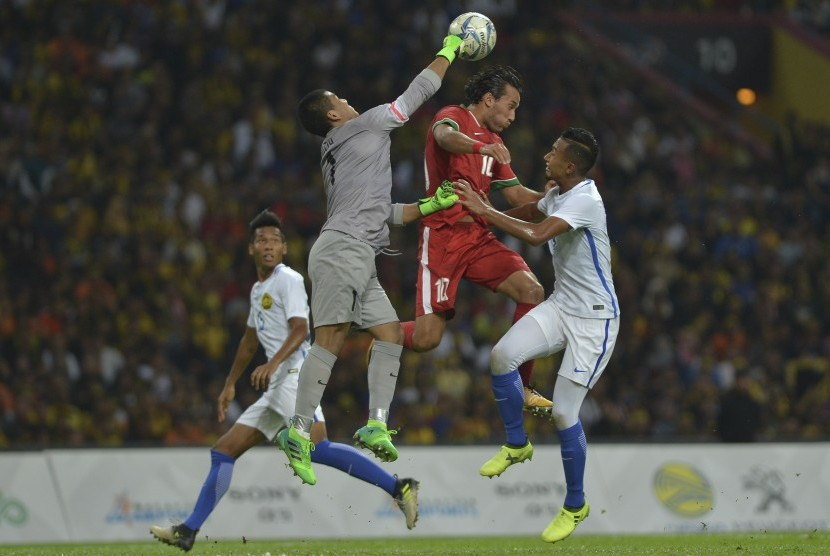 Pemain Timnas Indonesia U-22 Ezra Walian (tengah) berebut bola dengan pemain Timnas Malaysia U-22 Adam Nor bin Azlin (kiri) dan Kiper Muhammad Haziq bin Nadzli dalam babak semi final SEA Games XXIX Kuala Lumpur di Stadion Majlis Perbandaran Selayang, Malaysia, Sabtu (26/8).