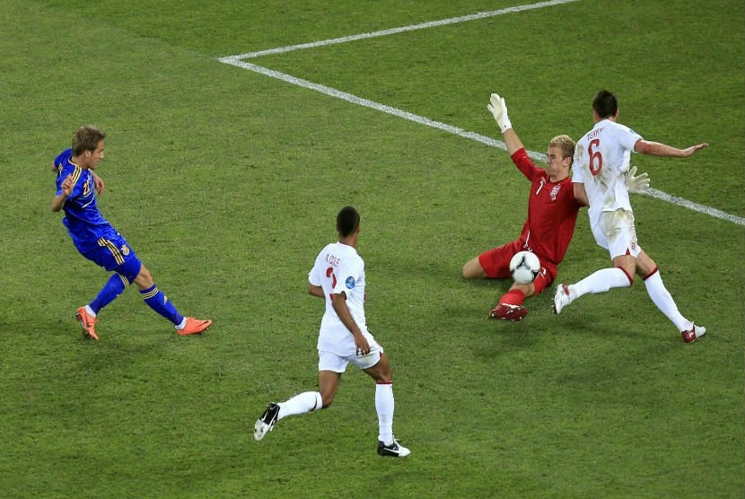 Pemain Ukrania Marko Devic menendang bola ke arah gawang yang ditepis oleh penjaga  gawang Inggris Joe Hart.  (Vadim Ghirda/AP)