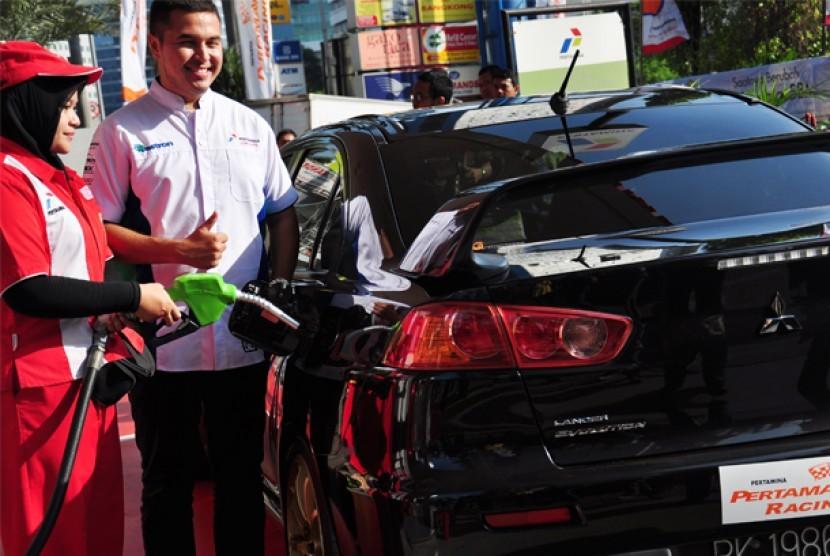Pembalap nasional, Rifad Sungkar (kanan), mengisi bahan bakar mobil pertamax racing saat acara peluncuran Pertamax Racing di Kuningan, Jakarta, Jumat (20/7).