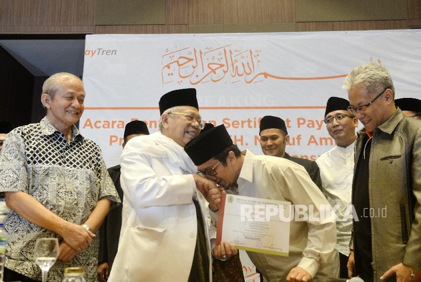 Pemilik PT Veritra Sentosa Internasional (VSI) atau PayTren, Yusuf Mansur (kedua kanan) mencium tangan Ketua Umum MUI KH Maruf Amin didampingi Sekjen MUI Anwar Abbas (kiri), dan Dirut PayTren Hari Prabowo (kanana) saat penyerahan Sertifikat Syariah DSN- MUI oleh MUI di Bogor, Jawa Barat, Senin (7/8).