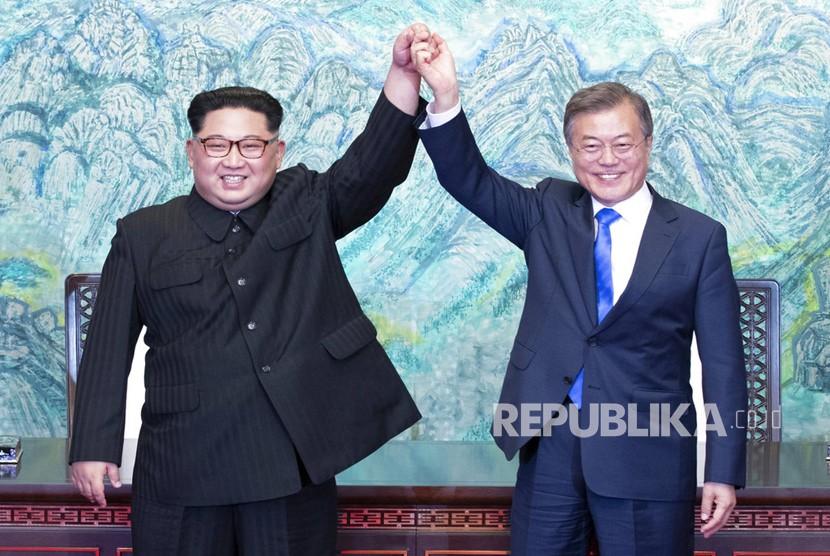 Pemimpin Korea Utara Kim Jong Un, kiri, dan Presiden Korea Selatan Moon Jae-in mengangkat tangan mereka setelah menandatangani pernyataan bersama di desa perbatasan Panmunjom di Zona Demiliterisasi, Korea Selatan, Jumat (27/4).