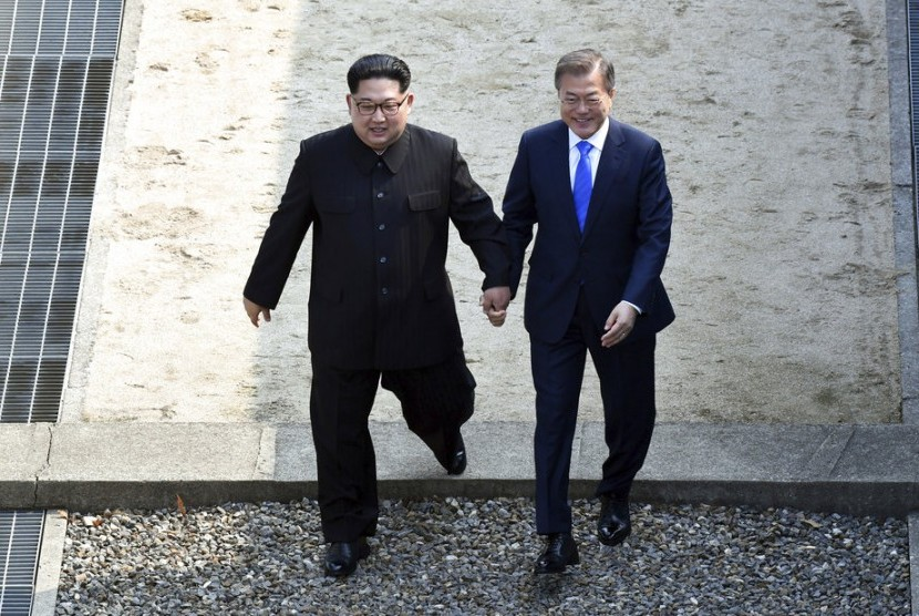 Pemimpin Korea Utara Kim Jong-un (kiri) dan Presiden Korea Selatan bergandeng tangan melangkah melewati perbatasan negara di Desa Panmunjom di Zona Demiliterisasi, Jumat (27/4).