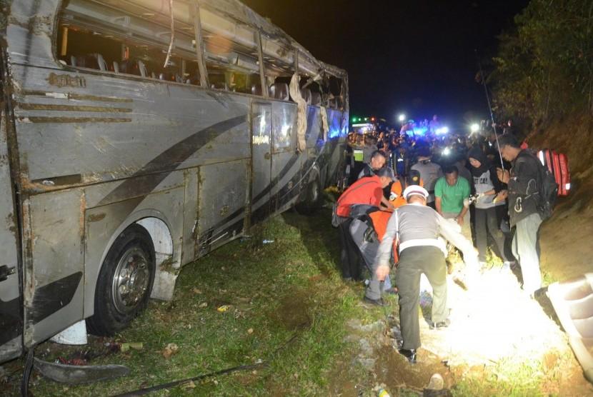 Petrugas mencari barang-barang berharga saat evakuasi kecelakaan bus pariwisata di tanjakan Emen, Kecamatan Ciater, Kabupaten Subang, Sabtu (10/2).