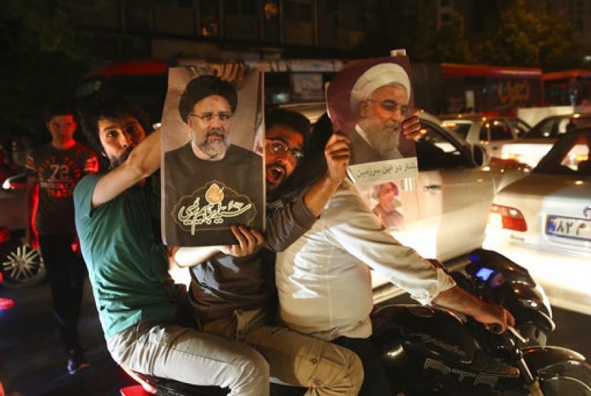 Pendukung Presiden Iran Hassan Rouhani (kanan) memegang posternya. Di kiri, seorang warga memegang poster rival terkuat Rouhani, Ebrahim Raisi saat kampanye 17 Mei 2017. Iran akan menggelar pemilu presiden pada Jumat, 19 Mei 2017.