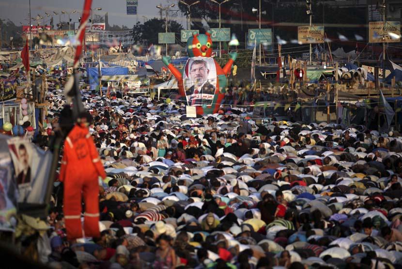 Pendukung Presiden Muhammad Mursi melaksanakan Shalat Idul Fitri memadati jalan raya di luar Masjid Rabaah al-Adawiya, Nasr City, Kairo, Kamis (8/8).  (AP/Khalil Hamra)