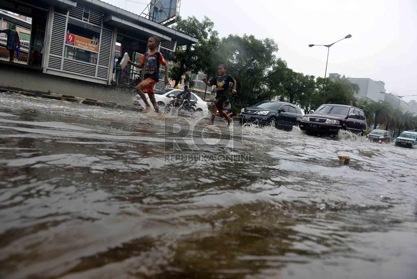 Sejumlah anak bermain air saat banjir di jalan gunung sahari, jakarta