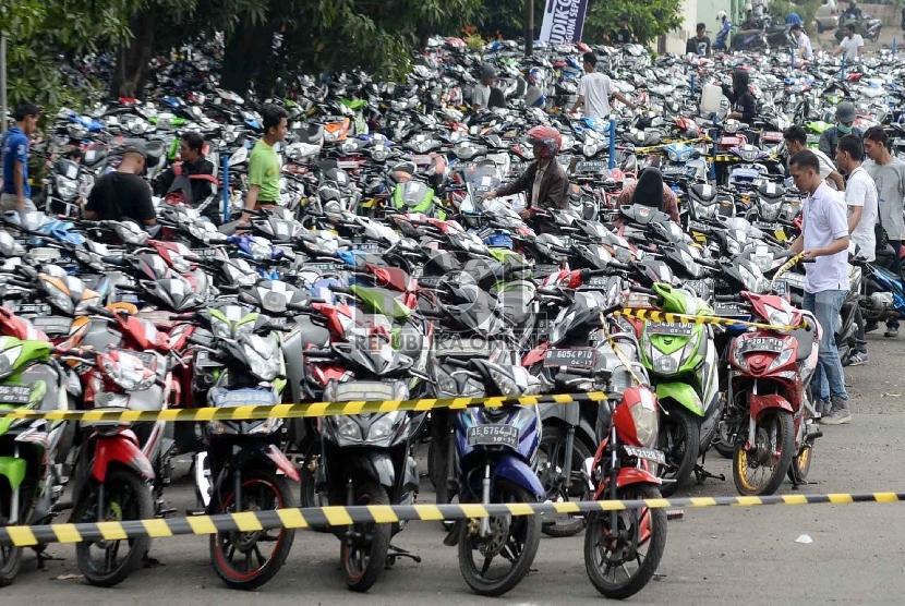 Pemudik motor gratis mengepak motor yang akan diangkut.