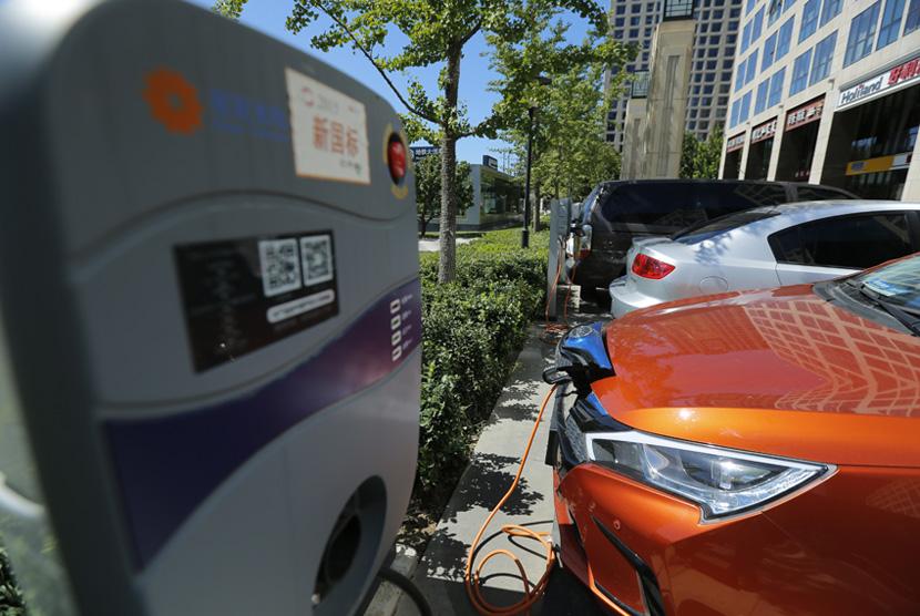 Pengisian kendaraan mobil berbahan bakar listrik di luar sebuah apartemen di Beijing, China, 11 September 2017.