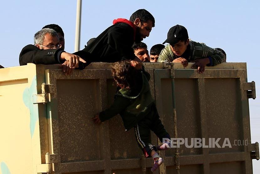 Pengungsi Irak di Mosul menarik lengan anaknya menaiki truk yang akan mengangkut mereka ke tempat yang lebih aman .