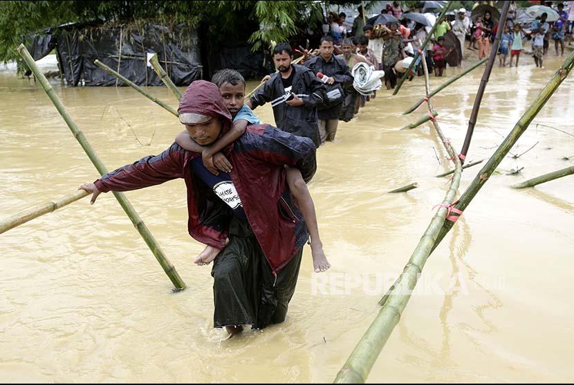 Pengungsi melintasi sungai yang meluap di kamp pengungsi Rohingya di Cox's Bazaar, Bangladesh, Selasa (19/9).