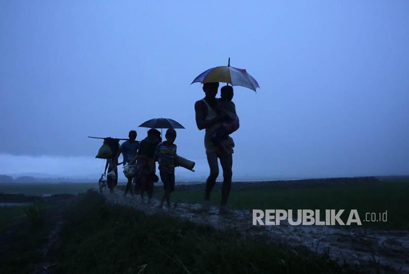 Pengungsi Rohingya berjalan di bawah hujan saat mereka tiba di perbatasan Bangladesh di Teknaf, Bangladesh, Sabtu (9/9).
