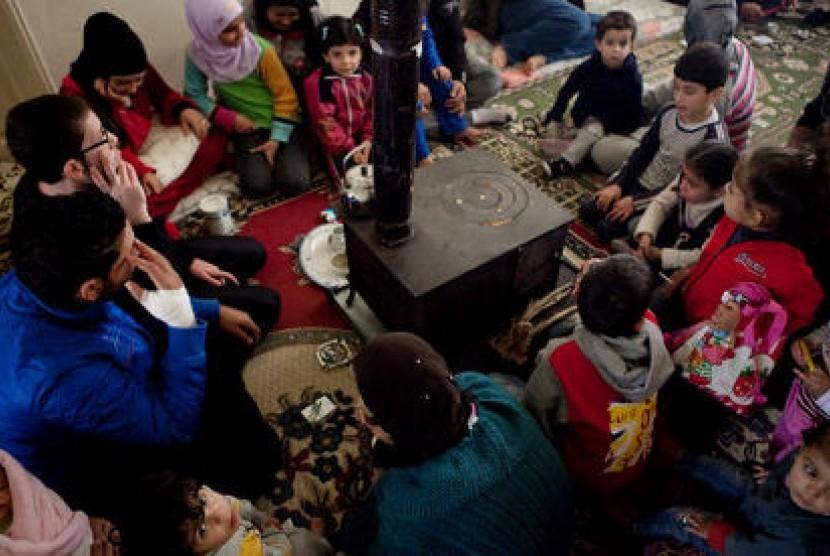 Pengungsi Suriah di Lebanon mengelilingi tungku untuk menghangatkan diri.