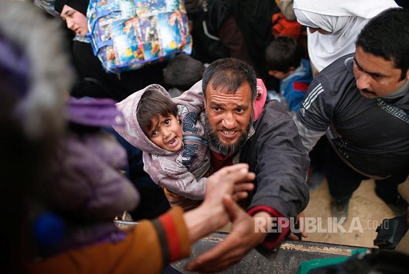 Pengungsi Irak di Mosul berusaha menaiki truk yang akan mengangkut mereka ke tempat yang lebih aman.