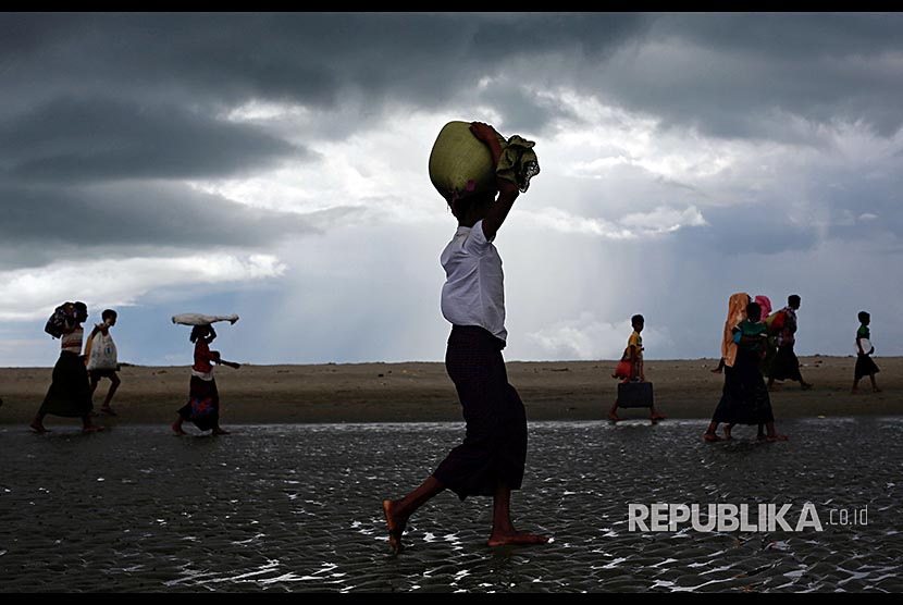Pengungusi Rohingya berjalan di pesisir Teluk Bengal, di Shah Porir Dwip, Bangladesh, Selasa (11/9)
