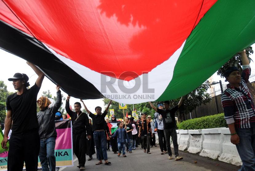 Pengunjuk rasa membawa bendera Palestina raksasa saat unjuk rasa beberapa organisasi Muslim di depan Kedubes Amerika Serikat (AS), Jakarta. (ilustrasi)