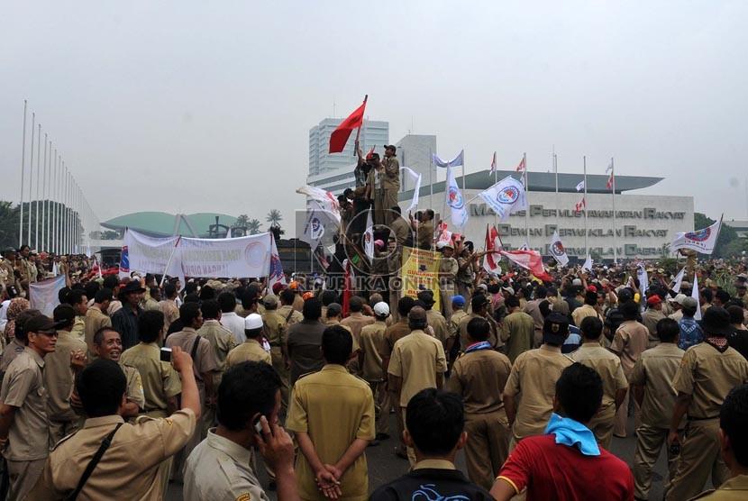 Pengunjuk rasa yang tergabung dalam Persatuan Perangkat Desa Indonesia (PPDI) dan Aliansi Desa Indonesia (ADI) menggelar aksi unjuk rasa di depan gedung Parlemen, Jakarta, Jumat (14/12).   (Republika/ Tahta Aidilla)