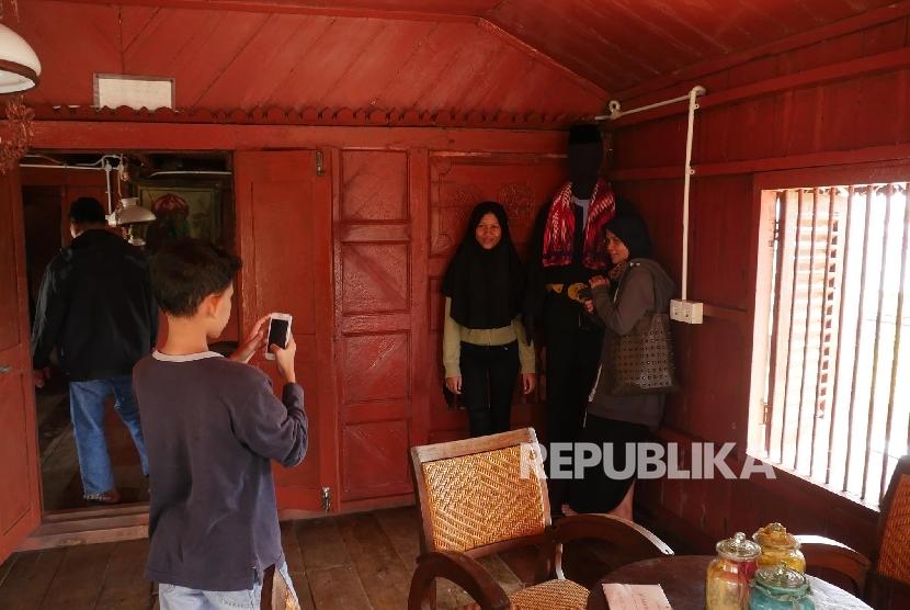 Pengunjung berfoto di replica badan si Pitung di dalam rumah si Pitung Jakarta, Ahad (16/4).