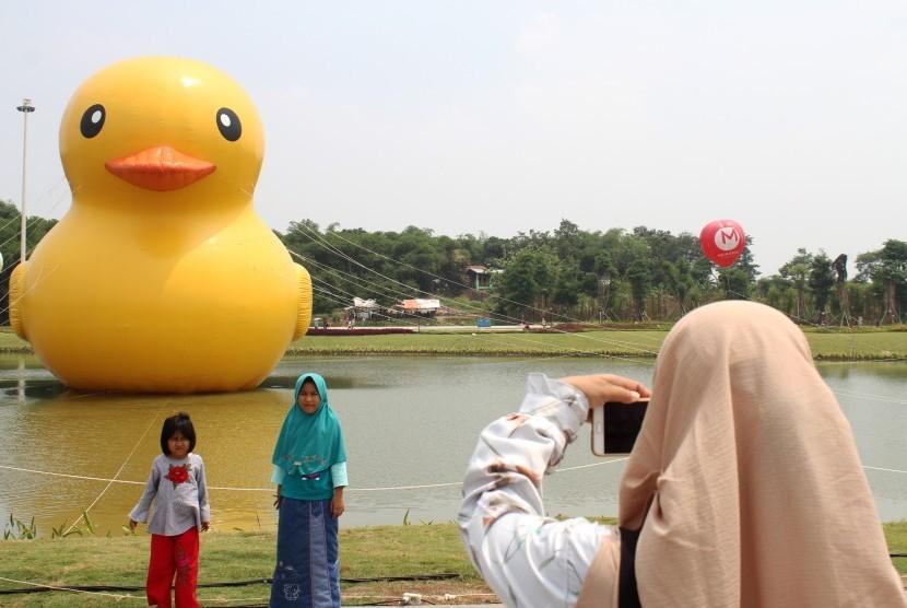 Pengunjung berpose foto dengan latar belakang patung bebek raksasa disela acara peluncuran Giant Yellow Duck, di Central Park Meikarta, Cikarang, Kabupaten Bekasi, Jawa Barat, Minggu (5/11).