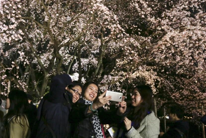 Pengunjung berswafoto dengan latar bunga sakura yang mekar di Rikugien Garden Tokyo, (27/3). Pengelola taman menyebut sudah 30 ribu orang datang untuk melihat bunga sakura.