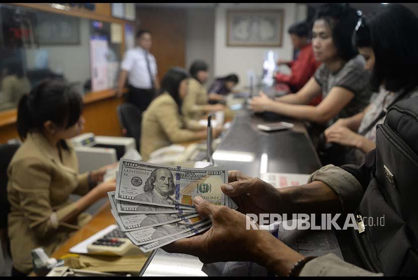 Pengunjung melakukan penukaran mata uang asing di jasa penukaran uang Ayu Masagung, Jakarta, Senin (23/4). Nilai tukar rupiah yang ditransaksikan antarbank di Jakarta, Senin (23/4), bergerak melemah 80 poin menjadi Rp13.943 dibandingkan posisi sebelumnya Rp13.863 per dolar AS.