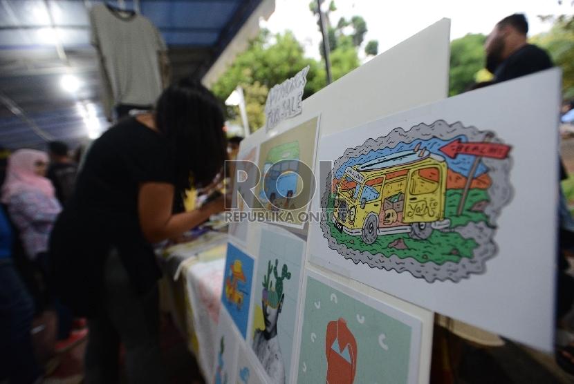 Pengunjung melihat-lihat cinderamata yang dijual saat Konser Perubahan Iklim yang diadakan di Taman Menteng, Jakarta, Ahad (6/12). (Republika/Raisan Al Farisi)