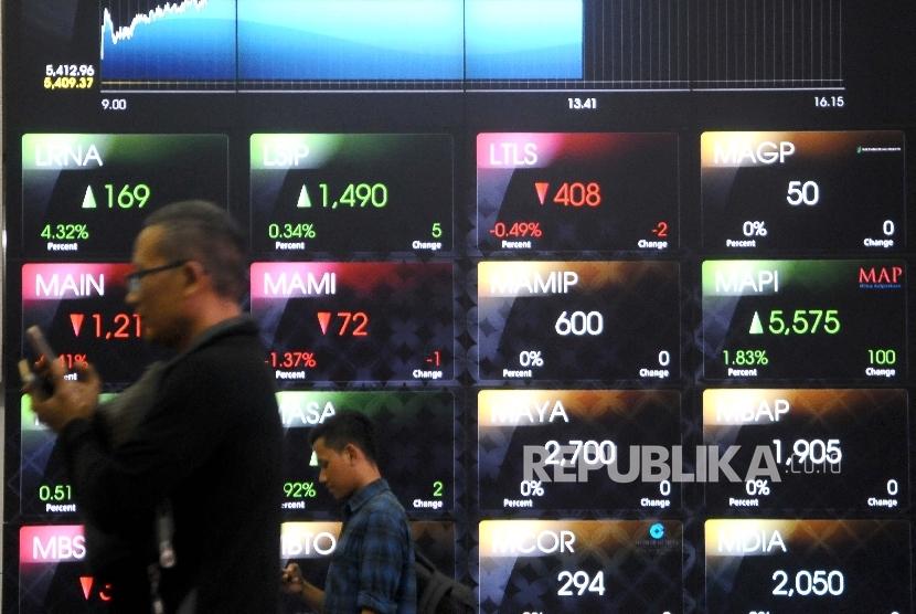 Pengunjung melintas di dekat layar pergerakan Indeks Harga Saham Gabungan (IHSG) di Gedung Bursa Efek Indonesia (BEI), Jakarta, Selasa (14/3).