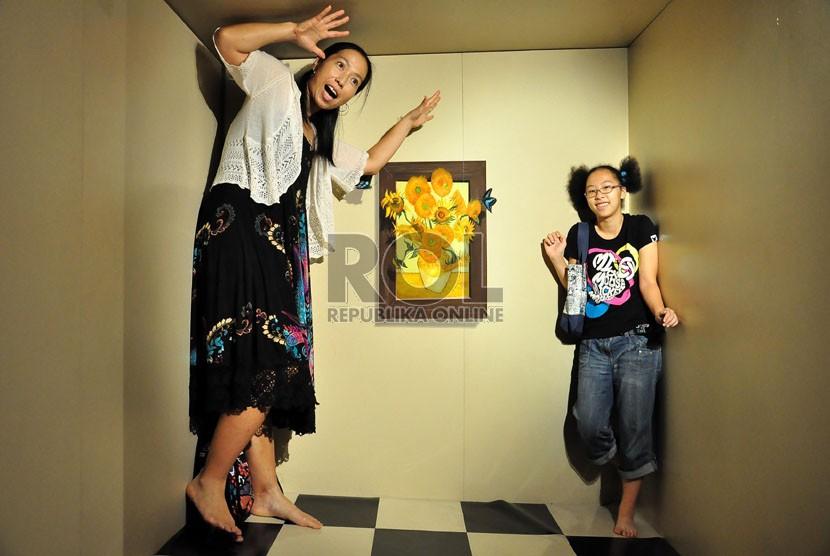 Pengunjung mencoba salah satu lukisan dalam pameran lukisan 3 dimensi Trick Art Japan di Grand Indonesia, Jakarta Pusat, Ahad (2/11). (Republika/Rakhmawaty)