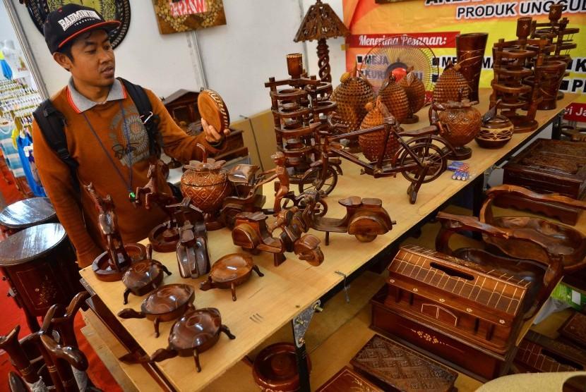 Pengunjung mengamati produk usaha kecil dan menengah (UKM) berupa cinderamata berbahan kayu. .