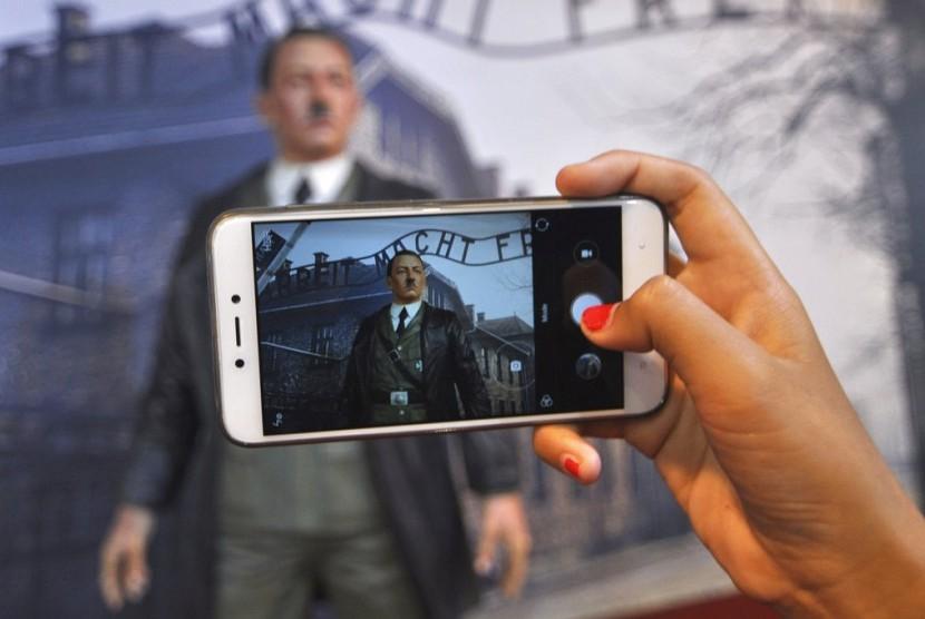Pengunjung mengambil foto patung lilin Adolf Hitler berlatar kamp kematian Nazi Auschwitz-Birkenau di Museum De Mata, Yogyakarta. Kini patung Hitler sudah tidak lagi ada di sana.