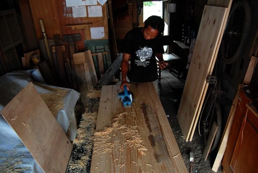 Pengusaha Usaha Kecil Menengah (UKM), Supri (30) menyerut papan pintu yang akan dijual di rumah produksi miliknya kawasan Lenteng Agung, Jakarta Selatan, Kamis (26/6). Dinas Koperasi Usaha Mikro Kecil dan Menengah (UMKM) meminta agar para pelaku UKM mening