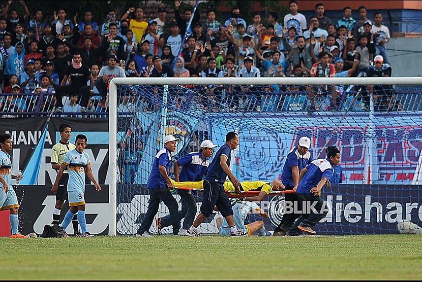 Penjaga gawang Persela Lamongan Choirul Huda ditandu petugas kesehatan ketika bertanding melawan Semen Padang dalam lanjutan Gojek Traveloka Liga 1 di Stadion Surajaya Lamongan, Jawa Timur, Minggu (15/10).