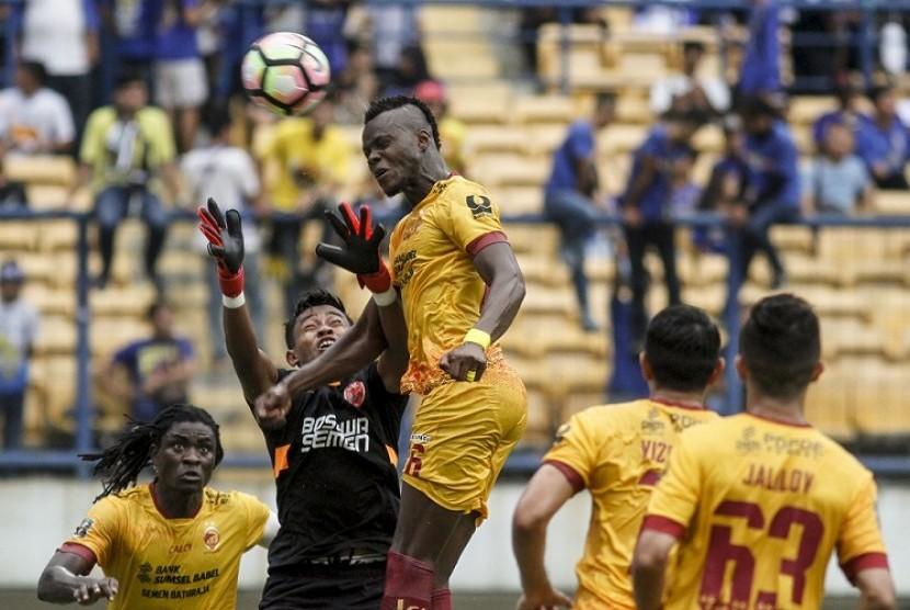 Penjaga gawang PSM Makassar Syaiful (kedua kiri) berusaha menghalau sundulan pemain Sriwijaya FC Mahamadou N'Diaye (tengah) pada laga lanjutan Grup A Piala Presiden 2018 di Stadion Gelora Bandung Lautan Api, Bandung, Jawa Barat, Ahad (21/1). Sriwijaya berhasil mengalahkan PSM dengan skor akhir 3-0.