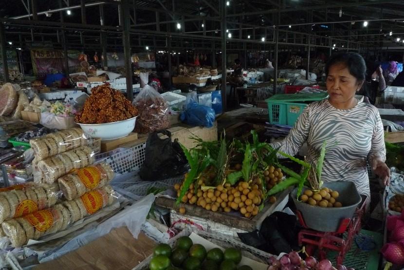 Penjual buah menimbang buah lengkeng di lokasi penampungan sementara pedagang Pasar Klewer di Solo, Jawa Tengah, Minggu (23/4).