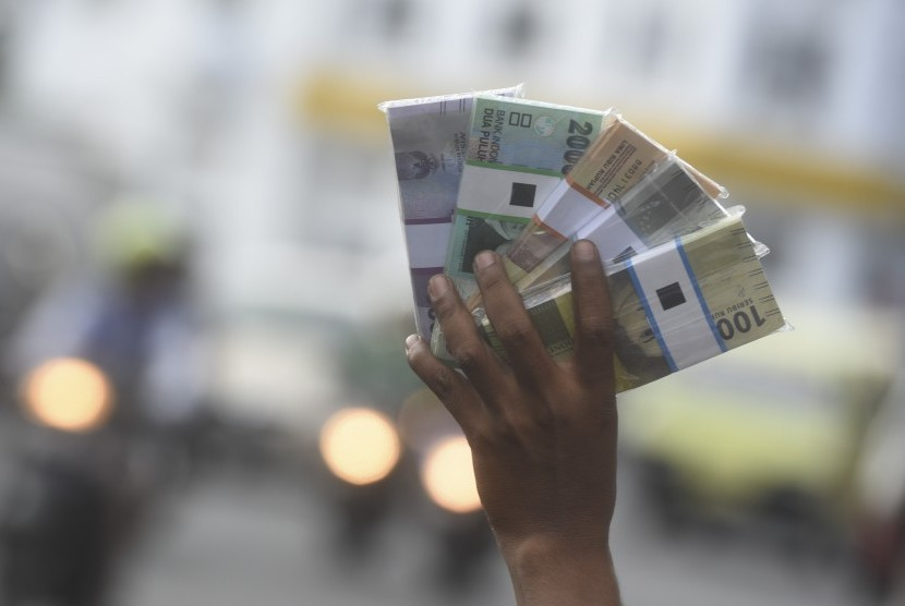 Penjual jasa penukaran uang baru menawarkan uang baru kepada pengguna jalan di pinggiran jalan, Surabaya, Jawa Timur, Selasa (6/6). Pada bulan Ramadan, para penjual jasa penukaran uang baru ramai bermunculan di pinggir-pinggir jalan, mereka menukarkan uang baru tersebut dengan tambahan 10 persen dari jumlah uang yang ditukarkan.