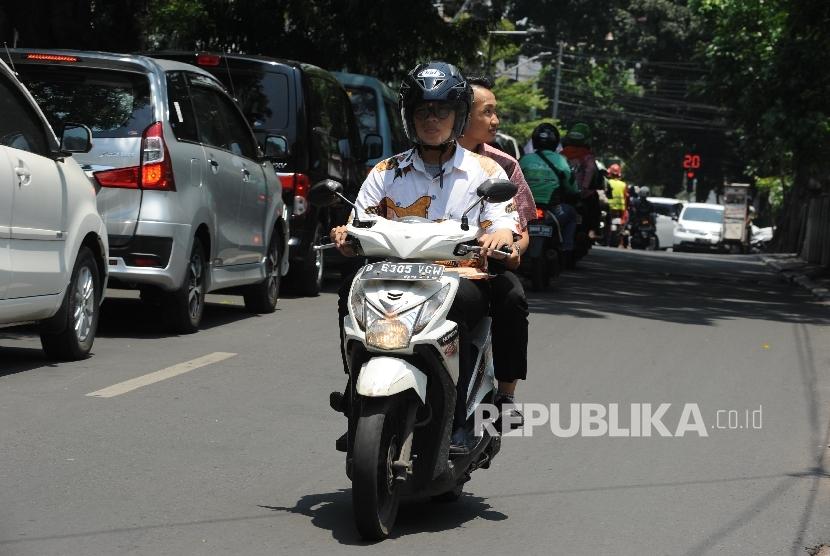Penumpang angkutan ojek online tidak menggunakan Helm di daerah Jalan Rawajati Barat, Jakarta, Rabu (22/09).