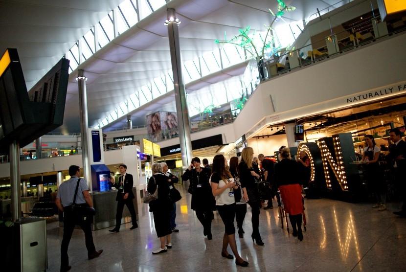 Penumpang melewati sederetan toko dan restoran di Bandara Heathrow, Inggris.