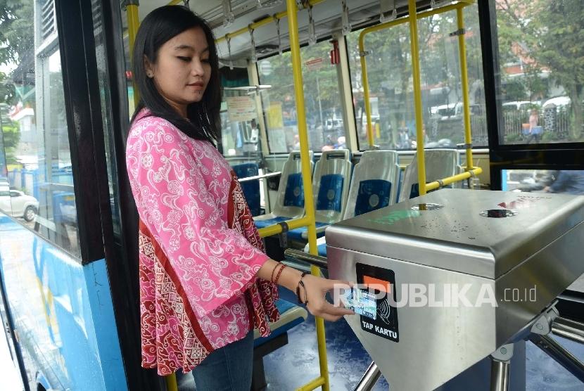 Penumpang menggunakan kartu Bandung Smart Car pada uji coba penggunaan tiket elektronik bus Trans Metro Bandung (TMB), di halte bus TMB Koridor II, Jalan Ahmad Yani, Kota Bandung, Jumat (11/3).(Republika/Edi Yusuf)