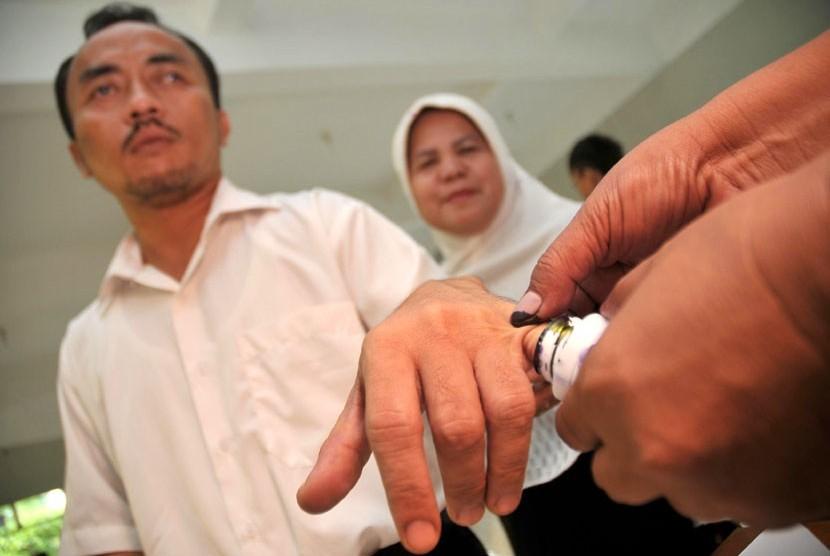 Penyandang tuna netra menggunakan hak pilihnya dalam Pilkada DKI Jakarta 2012-2017 di TPS 11, Cawang, Jakarta Timur, Rabu (11/7).   (Aditya Pradana Putra/Republika)