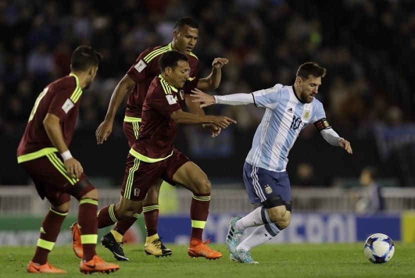 Penyerang Argentina Lionel Messi (kanan) melewati para pemain Venezuela dalam laga kualifikasi Piala Dunia 2018 zona Conmebol.