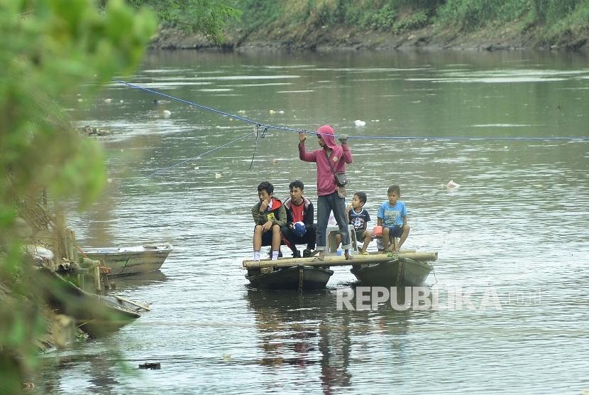 Anak sekolah menyebrangi sungai untuk tiba di sekolahnya yang jauh (ilustrasi)