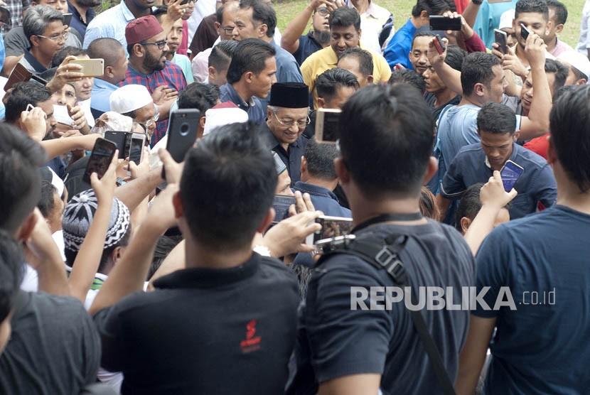 Perdana Menteri ke-7 Malaysia Tun Mahathir Mohamad (tengah) didamping jemaah berjalan seusai Salat Jumat di Masjid Negara, Kuala Lumpur, Malaysia, Jumat (11/5).