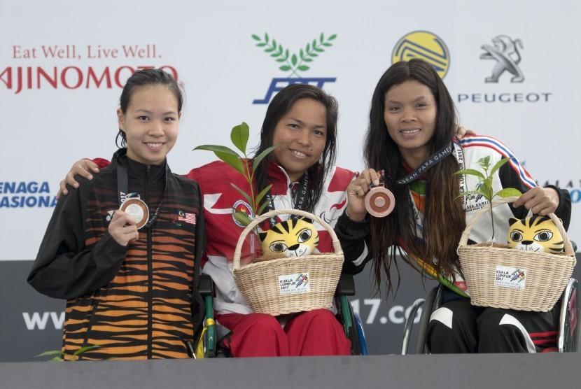 Perenang Indonesia Gusmalayanti (tengah) disamping perenang Malaysia Lim Carmen (kiri) dan perenang Thailand W Wilasini memperlihatkan medali masing-masing dalam nomor 100 meter renang gaya punggung putri Asean Para Games IX Kuala Lumpur, di National Aquatic Centre, Kuala Lumpur, Malaysia, Kames (21/9).