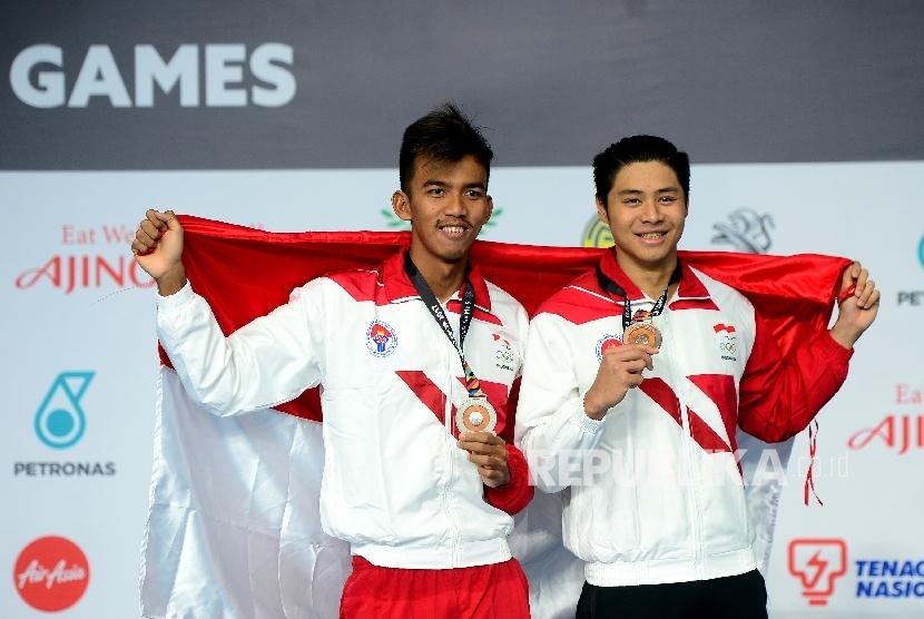 Perenang Indonesia Triady Fauzi Sidiq (kiri) bersama Glenn Victor Sutanto saat pengalungan medali cabang renang nomor 100m gaya kupu-kupu di national Aquatic, Komplek Stadion Bukit Jalil, Malaysia, Rabu (23/8).